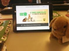 Maskottchen Edith vor einem Tablet bei der Präsentation der 27. Bundes-Rammlerschau in Meinhard-Grebendorf